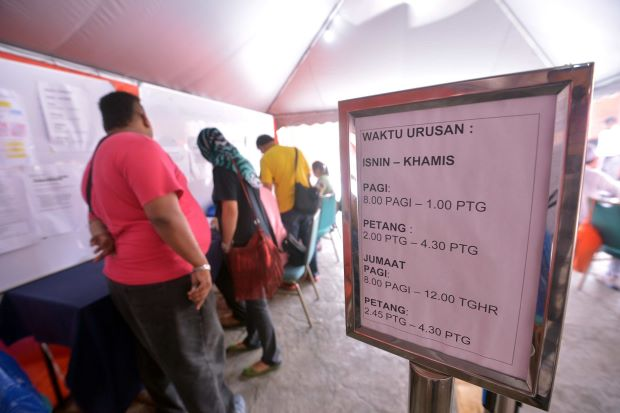Making the deadline: Employers getting their papers in order at the One-Stop Centre in Putrajaya.