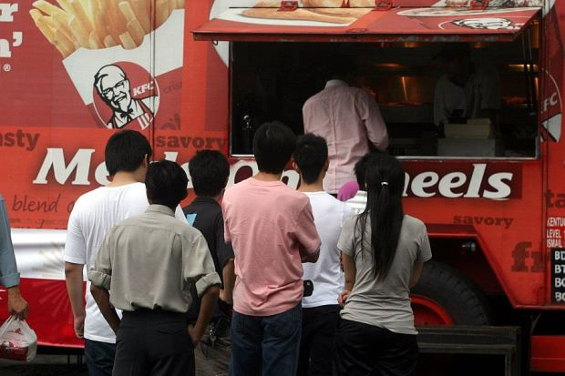 People queuing up at a mobile fast food outlet. - filepic