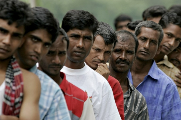 This file photo taken on December 25, 2007 shows Bangladeshi migrant workers waiting in line for food donated by a goodwill charity group for Christmas outside the Bangladeshi High Commission in Kuala Lumpur. — AFP pic