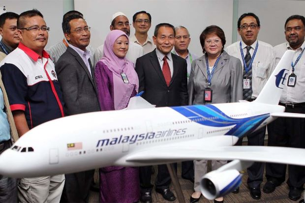 MAS' Ahmad Jauhari (centre) with staff on Wednesday.