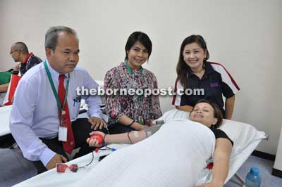 (From left) Martin, Alina and Hadiah with a donor during the blood donation drive.