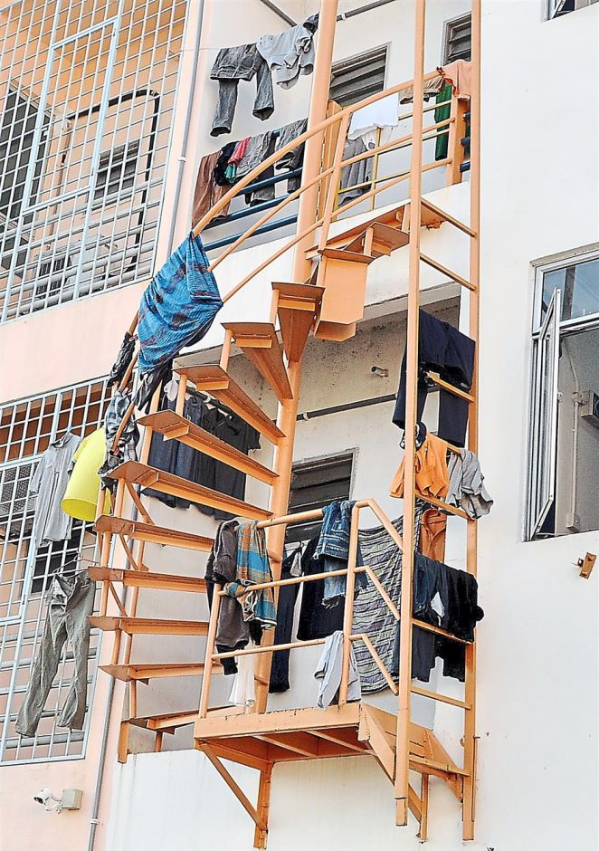 Foreign workers hang their clothes all along an emergency exit at one of the shoplots.