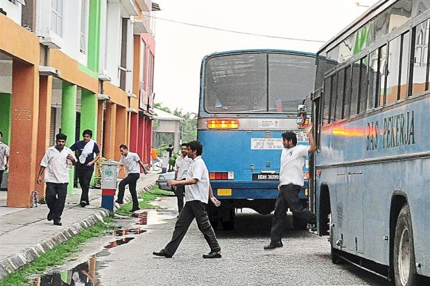 Foreign workers getting off factory buses which transport them to and fro their workplaces.