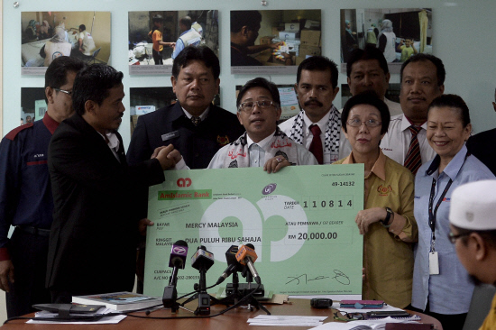 Azih Muda presents a cheque to Mercy Malaysia Executive Council Member Ar Mohamad Ayof Bajuri. SUNPIX by ADIB RAWI YAHYA