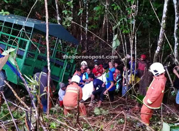 The uninjured oil palm estate workers help firefighters to extricate the deceased from beneath the wagon.