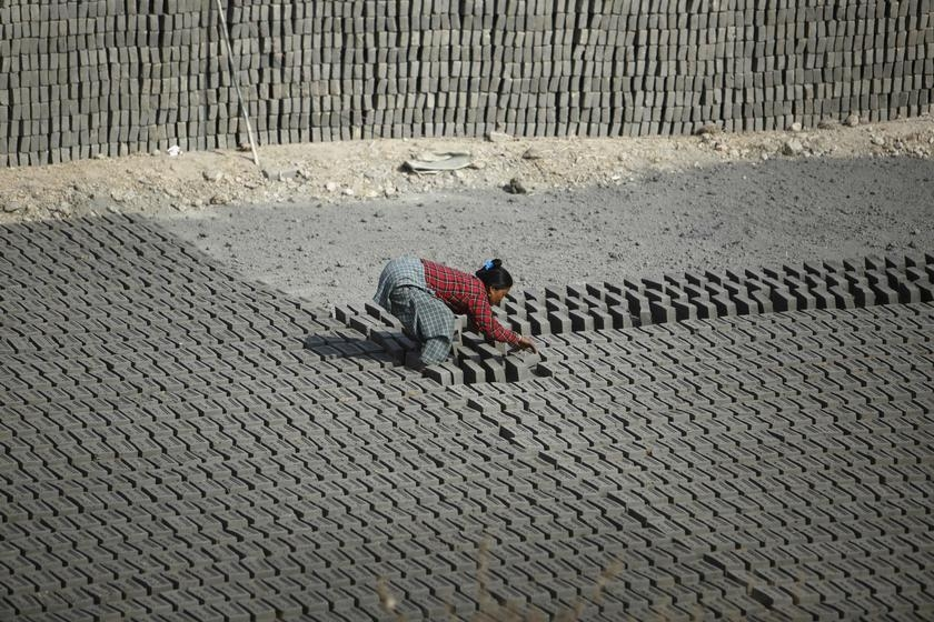 A woman flips bricks laid out to dry out in the sun before baking them at a brick factory in Lalitpur. India and Malaysia are two of the Asia Pacific countries that share the same bottom half rating of CCC on the Global Slavery Index 2014. — Reuters pic