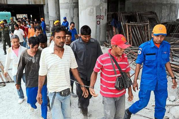 Cornered: Some of the foreign workers rounded up in the raid on a construction site in Butterworth.