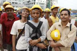 © AP Immigrants and robots are not taking over jobs., but rather are performing almost all menial, unwanted work, the IMF said. In this May 11, 2009, file photo, foreign construction workers line up outside a building site for their transport home in Kuala Lumpur, Malaysia.