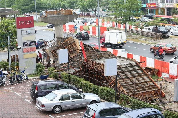 Construction mishap: Motorists passing by the collapsed bridge at Jalan Genting Klang.
