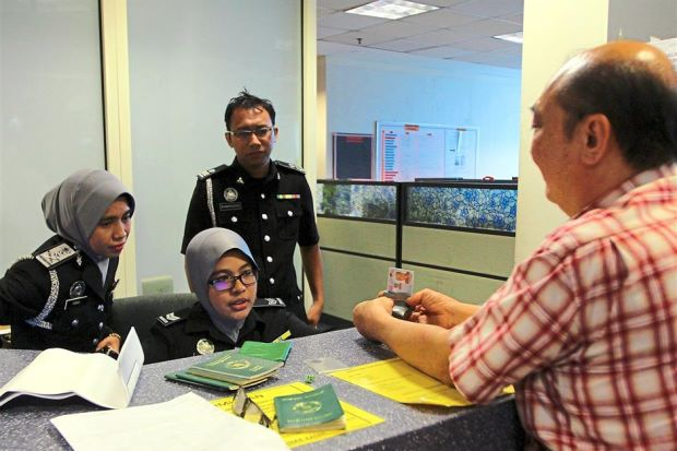 Good old days: A file picture of an employer applying for his foreign worker's permit at an immigration counter in Putrajaya.