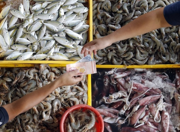 A seafood stall keeper returns change to a customer at a market in Kuala Lumpur August 27, 2013. — Reuters pic