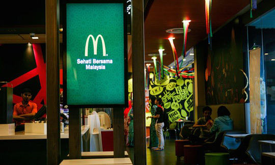 A McDonald's logo is seen in a restaurant in Shah Alam, outside Kuala Lumpur. Migrants say they suffered labour abuses while working in the firm's restaurants in Malaysia. Photograph: Mohd Samsul Mohd Said/Getty Images