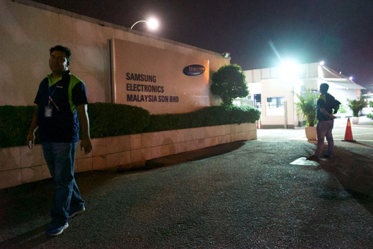 Workers (not interviewed by the Guardian) at the entrance to the Samsung plant in Port Klang. Photograph: Pete Pattisson