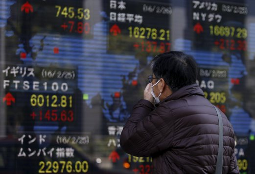 A pedestrian looks at an electronic board showing the stock market indices of various countries outside a brokerage in Tokyo, Japan, February 26, 2016. Asian shares made guarded gains on Friday as a gathering of world finance leaders provided a welter of reassuring comments, but little in the way of actual policy stimulus. REUTERS/Yuya Shino